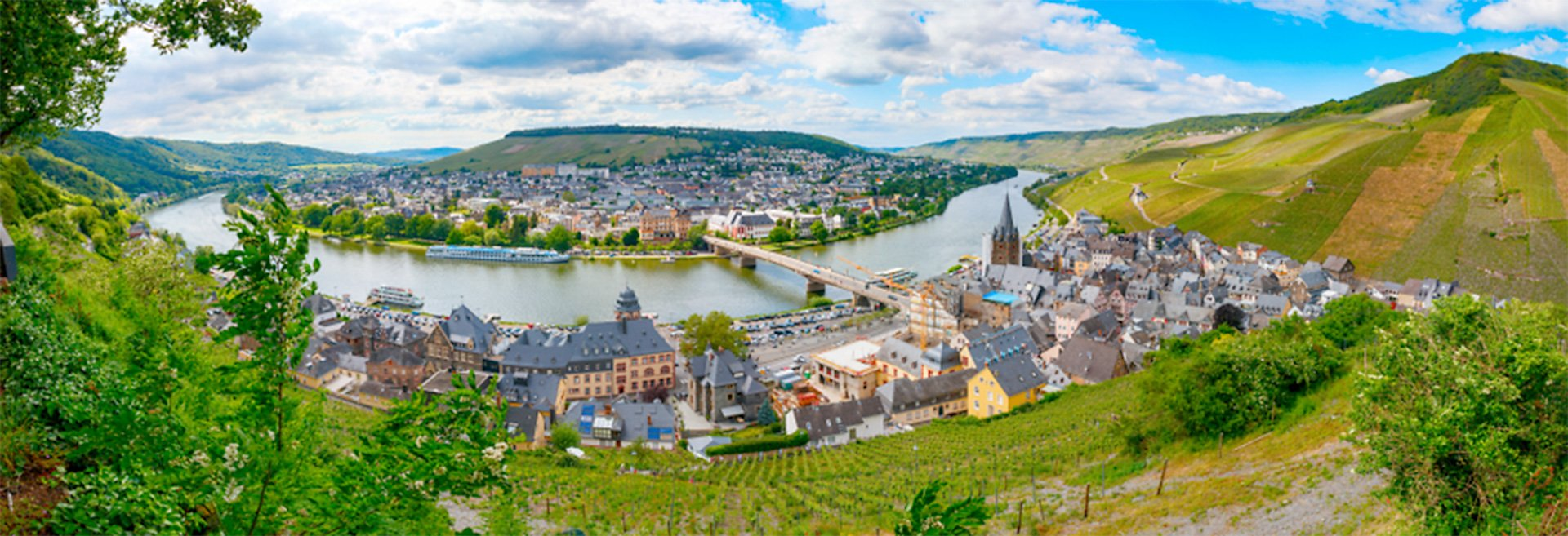 Panoramic view of Bernkastel-Kues and the Moselle river with the surrounding vineyards of the Moselle-valley on a sunny afternoon
