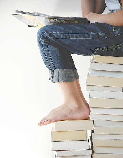 Student on top of a stack of books