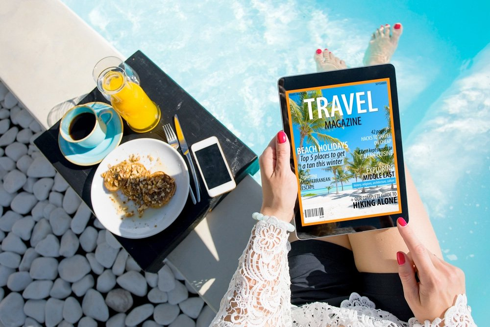 Poolside reading a Travel Magazine on a tablet